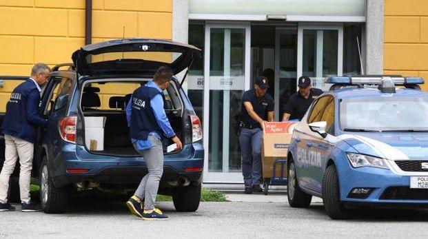 Gli investigatori della Mobile portano via materiale dagli uffici della Secam (Anp)
