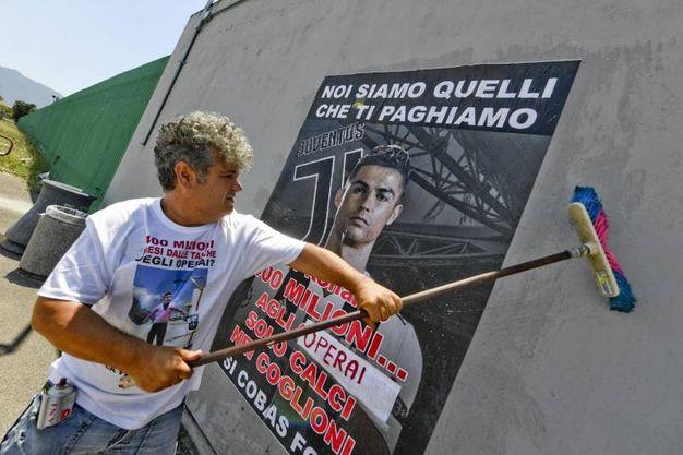 Un operaio affige un manifesto all'esterno dello stabilimento FCA di Pomigliano (Ansa)