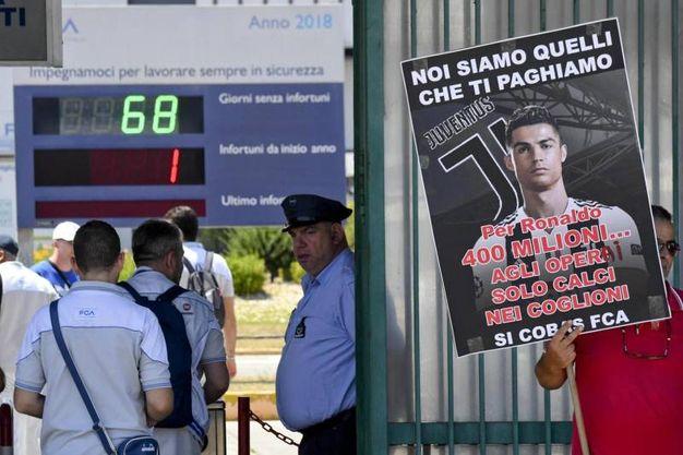 Un manifesto affisso sui muri dello stabilimento FCA a Pomigliano. Dietro, il tabellone degli infortuni (Ansa)
