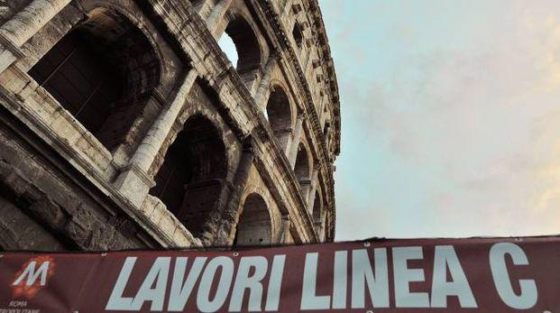 Un cartello che indica i lavori per la metro C davanti al Colosseo (Ansa)