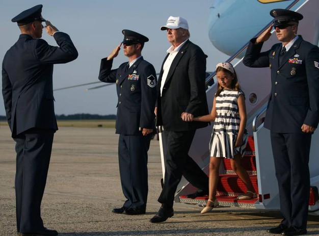 Donald Trump prende per mano la nipotina Arabella Kushner arrivando a Washington a bordo dell'Air force one (Ansa)
