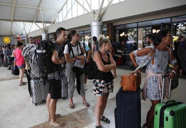 Turisti in attesa del volo (Ansa)