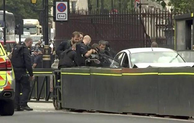 La polizia fa scendere dalla macchina l'uomo che si è schiantato contro le barriere del Parlamento a Londra (Ansa)