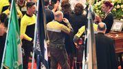 I pompieri omaggiano i feretri (Ansa)