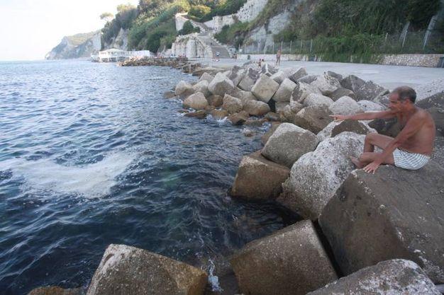 Un bagnante indica la macchia formata dalle alghe (Foto Antic)
