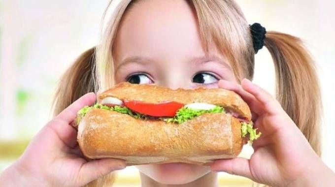 Una bimba mangia un panino, foto generica