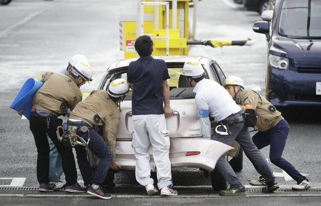 Alcuni soccorritori intervenuti a Osaka per il tifone Jebi (Ansa)