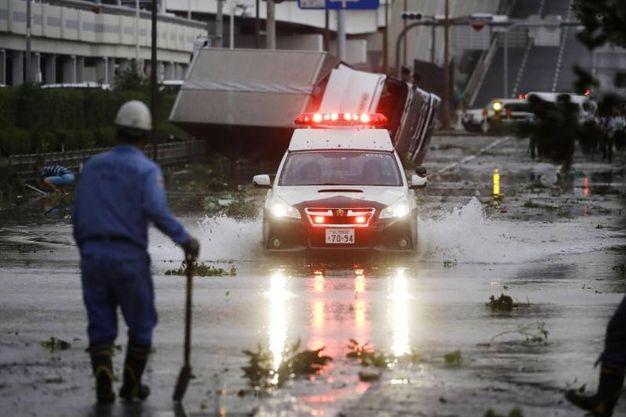 Una macchina della polizia attraversa una strada allagata per il tifone Jebi a Osaka (Ansa)