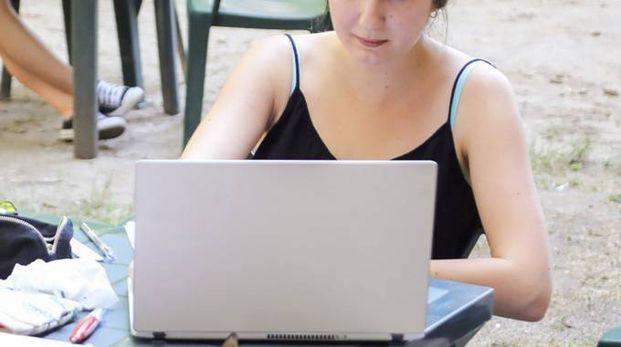 AL COMPUTER Una ragazza con il suo portatile (foto d'archivio)