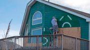 Un uomo installa delle travi di legno alle finestre della sua casa nel North Carolina (LaPresse)