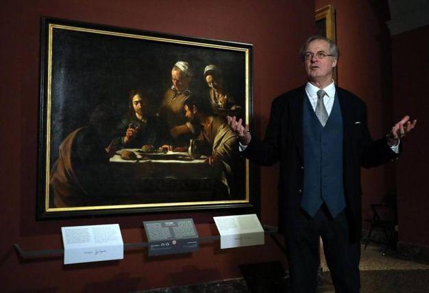 """Il direttore della Pinacoteca di Brera James Bradburne davanti a """"La cena di Emmaus"""" di Caravaggio (foto Ansa)"""