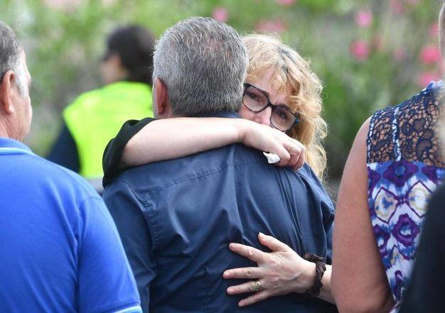 L'abbraccio fra i parenti delle vittime (Foto Ansa)