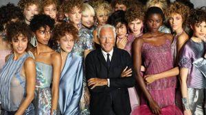 Armani alle sfilate milanesi circondato da modelle (Ansa)