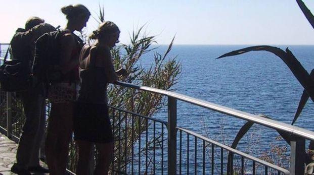 Turisti affacciati sul mare lungo un sentiero delle Cinque Terre: una sensazione inimitabi