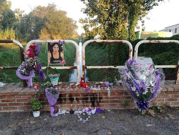 Fiori e candele sul ponticello vicino al canale dove è stato trovato il corpo (Ansa)
