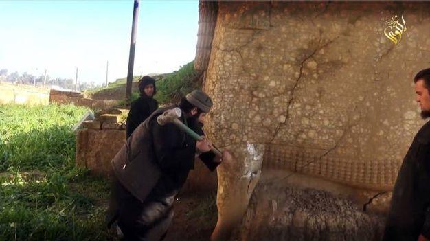 I terroristi dell'Isis distruggono la statua di Lamassu, una divinità assira, in Iraq (Afp)