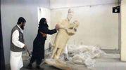 I terroristi dell'Isis distruggono una statua nel museo di Mosul, nord Iraq (Afp)