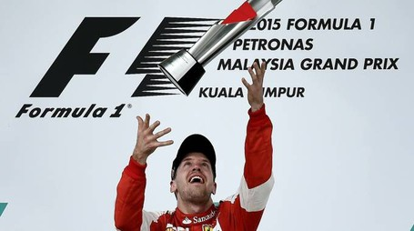 Ferrari's German driver Sebastian Vettel throws the trophy as he celebrates on the podium after winning the Formula One Malaysian Grand Prix in Sepang on March 29, 2015.  AFP PHOTO / MANAN VATSYAYANA