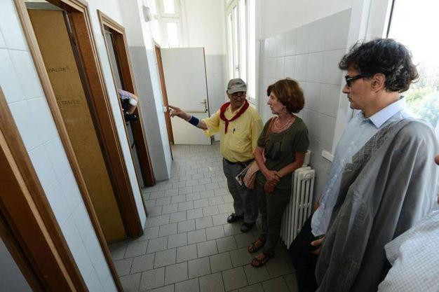 Arnaldo Cestaro, Enrica Bartesaghi (madre di Sara, una delle ragazze ferite) e Lorenzo Guadagnucci, tre 'reduci' del pestaggio da parte delle forze dell'ordine nella scuola Diaz durante il G8 di Genova la notte del 21 luglio 2001, tornano nell'istituto nel 2013 (Ansa)