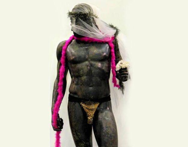 Uno dei Bronzi di Riace con il velo da sposa, il tanga leopardato e il boa (Ansa)