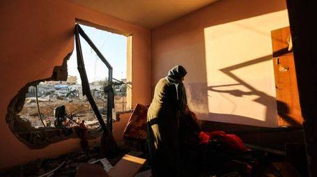 Una donna palestinese nella sua casa distrutta a Gaza (Afp)