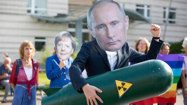 Un attivista tedesco con la maschera di Putin (Ansa)