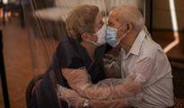 Due anziani si baciano con la mascherina attraverso un telone di plastica in una Rsa