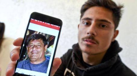 Un figlio di Raffaele Russo mostra la foto del padre, scomparso in Messico (Ansa)