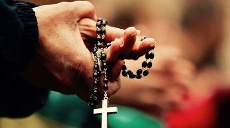 Il rosario tra le mani di un religioso in preghiera