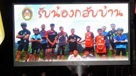 I bambini salvati in Thailandia su un maxischermo (Afp)