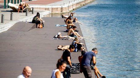 Milano, persone si abbronzano lungo la darsena (LaPresse)