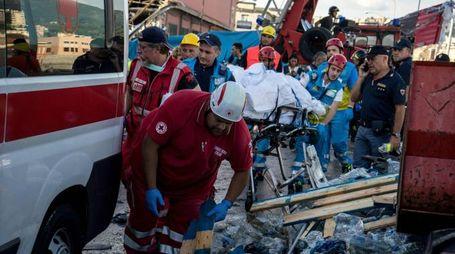 I soccorritori con uno dei corpi recuperati dalle macerie del ponte Morandi (Lapresse)