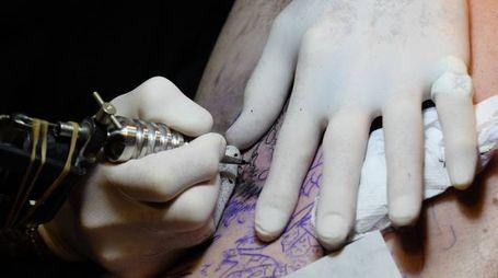 Un tatuatore al lavoro (Newpress)